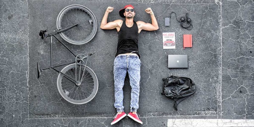 Man in Black Tank Top Laying on Gray Concrete Surface